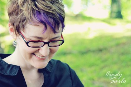 author jody wallace with a hank of purple bangs looking at the ground where she probably just dropped something